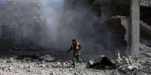 Un« casque blanc» inspecte un bâtiment touché par une frappe aérienne, dans le quartier rebelle de Saqba, dans la Ghouta orientale, en Syrie, le 23 février.