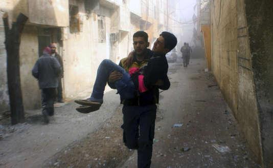 Un membre de la défense civile porte un jeune homme blessé lors d'un bombardement, dans la Ghouta orientale, le 24 février.