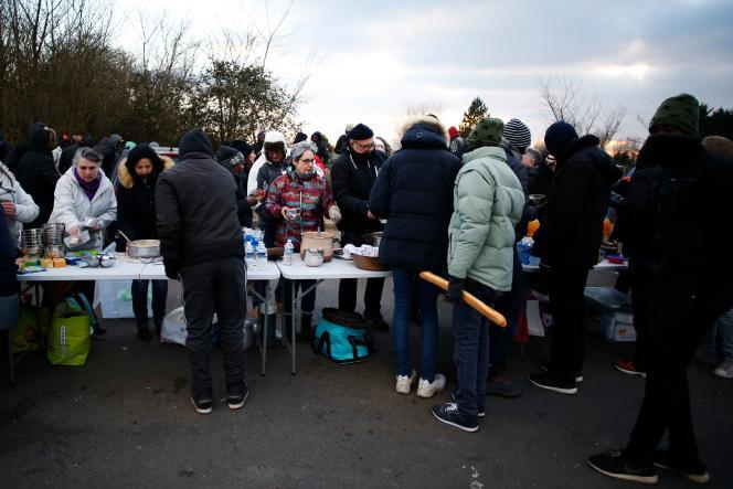 Des habitants distribuent de la nourriture aux migrants, à Ouistreham (Calvados), le 26 février.