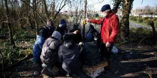 Un habitant de Ouistreham (Calvados) distribue de la nourriture à un groupe de migrants sur le port, en février.