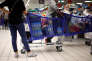 Customers stand next to shopping trolleys as they shop in a Carrefour hypermarket in Nice, France, April 6, 2016. REUTERS/Eric Gaillard/File Photo GLOBAL BUSINESS WEEK AHEAD PACKAGE - SEARCH 'BUSINESS WEEK AHEAD MAY 23' FOR ALL IMAGES - S1BETFPFMEAA
