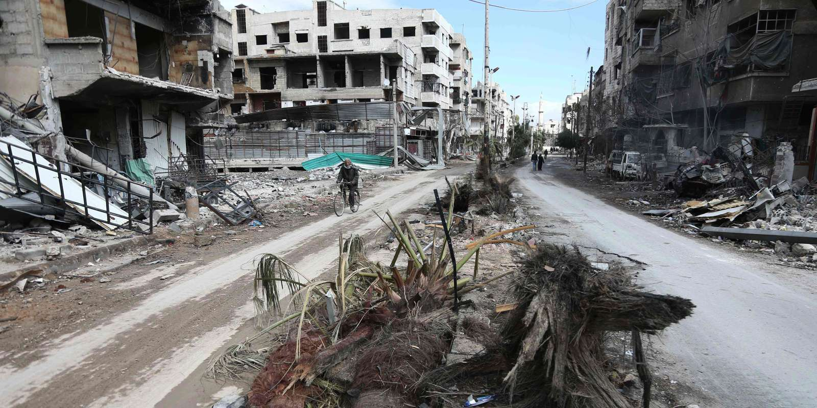 CORRECTION / TOPSHOT - A Syrian man cycles past destroyed buildings in the rebel-held town of Hamouria, in the besieged Eastern Ghouta region on the outskirts of the capital Damascus, on February 27, 2018. A humanitarian