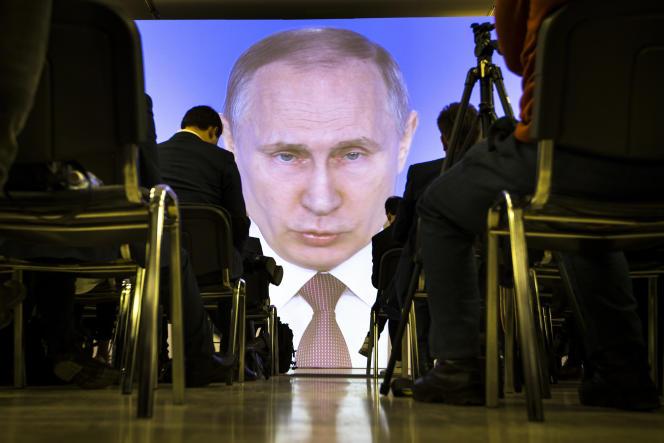 Vladimir Poutine sur l'écran de retransmission de la salle de presse lors de son discours annuel au Parlement, à Moscou, le 1er mars.