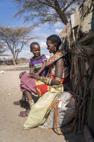 JernesaLekiloi, 28 ans, assise avec un de ses cinq enfants devant leur maison, à Mopukori, en février 2018.