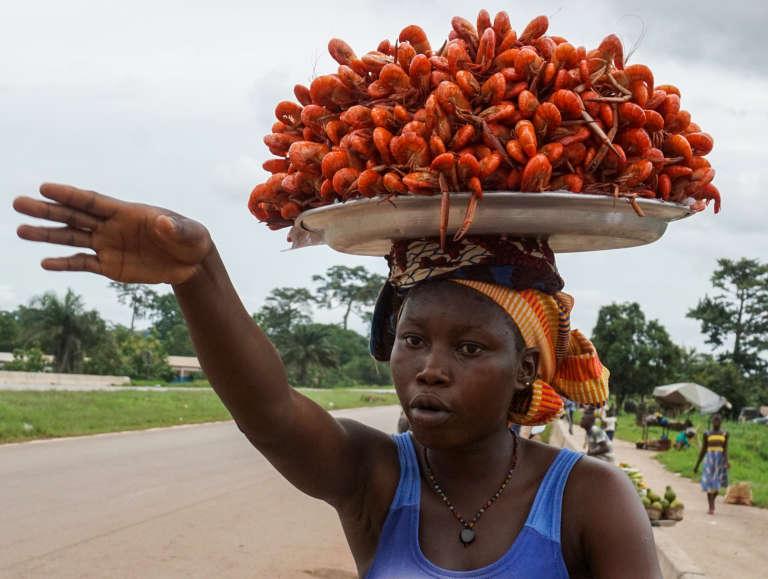 Une vendeuse de langoustines sur le bord de la route au nord d'Abidjan, en juin 2017.Des « femmes travailleuses » issues de l'administration, du milieu agricole et du secteur informel ont créé leur syndicat, pour que leurs préoccupations soient véritablement prises en compte.