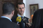 This photo provided by the official Facebook page of the Syrian Presidency, Syrian President Bashar Assad, center, speaks with reporters, in Damascus, Syria, Sunday, March 4, 2018 . Assad vowed Sunday to continue with a military offensive in a rebel-held region near the capital, as troops and allied militias captured a number of villages and towns in the besieged region, in their largest advance since a wide-scale operation began last month. (Syrian Presidency Facebook Page via AP)