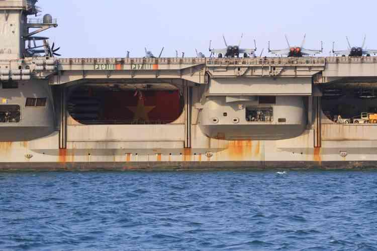 Un drapeau national vietnamien a été installé dans un hangar du porte-avions. Les tensions sont fortes en mer de Chine méridionale, où Pékin continue de construire des îles artificielles capables d'accueillir des installations militaires.