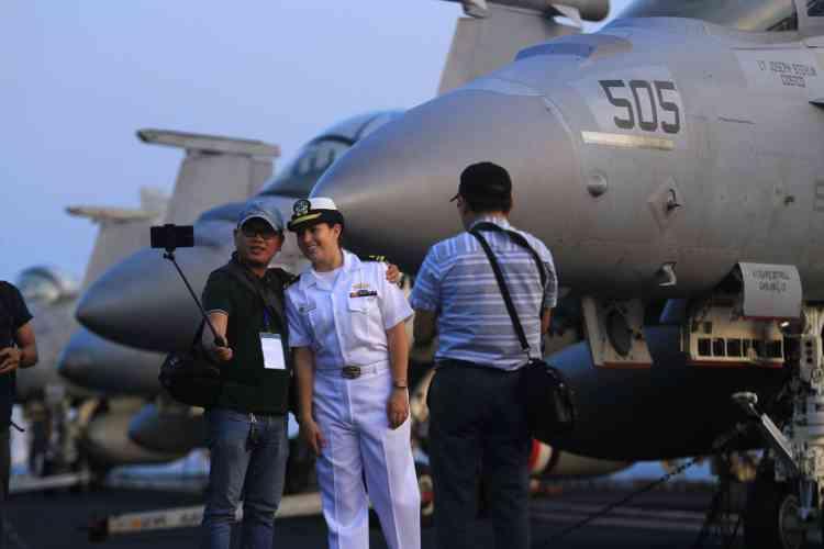 Un officier américain pose à côté d'un photographe vietnamien. Lors de la visite seront également organisés des matchs amicaux de basket-ball et de football entre des marins américains et des Vietnamiens, ainsi qu'une visite d'orphelinat et des concerts.