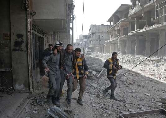 Des« casques blancs» syriens aident un blessé, à Hammouria, dans la Ghouta orientale, le 6 mars.