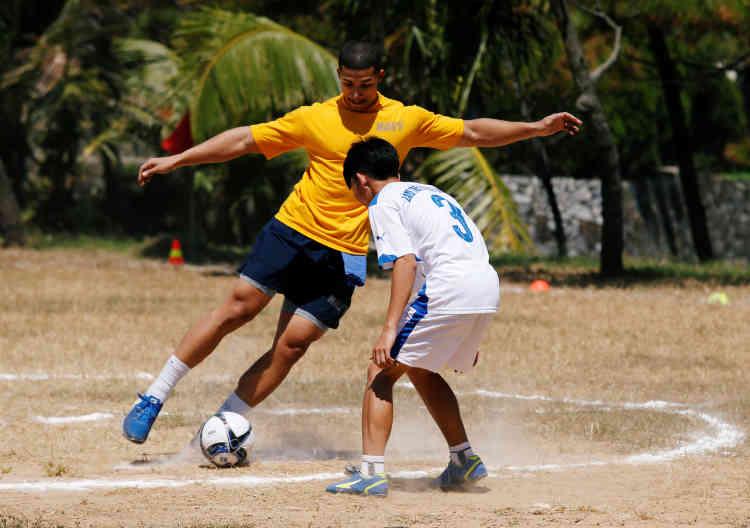 Un marin américain joue au football avec un garçon lors de sa visite au village d'enfants en détresse de Danang.