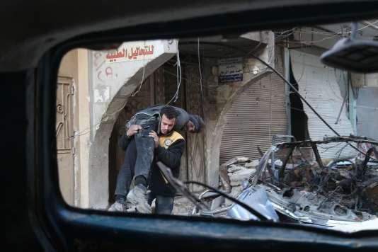 Un membre des casques blancs secourt une femme blessée dans la ville d'Hamouria, dans la Ghouta orientale, le 7 mars 2018.