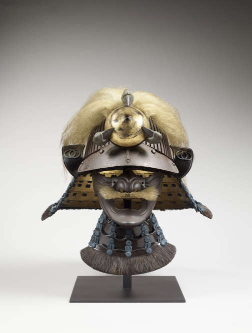 """«Le casque, aux armes de la famille des daimyos de Tatsuno, dans la province d'Harima, est composé de lamelles de fer verticales assemblées. Il présente une visière et un ornement au devant (""""maedate""""), un joyau doré tenu dans une griffe prolongée d'une longue touffe de poils qui recouvre le casque – signe qu'il s'agit de la griffe d'un dragon. Cet animal puissant et agile déclenche le tonnerre et l'orage, selon la mythologie chinoise. La moustache est en poil d'ours, comme pour s'attribuer les vertus de cet animal sauvage, courageux et féroce.»"""
