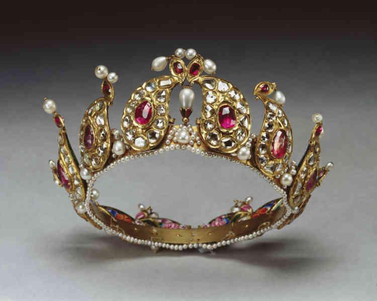«Cette tiare à décor de pierres précieuses et d'émail peint fut offerte à la reine Victoria par le dirigeant de Mascate, capitale d'un petit Etat de la péninsule arabique, dont le sultan entretint des rapportsétroits mais aussi complexes avec les souverains qajars : affilié à leur pouvoir, il n'eut de cesse de s'affranchir de leur tutelle. Pour autant, il passa de nombreuses commandes d'objets précieux en Iran, parmi lesquels cette tiare, qu'il offrit à la reine Victoria, tant pour célébrer son avènement que pour obtenir ses faveurs diplomatiques.»