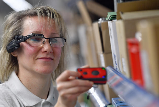 Une employée sourde de la firme Schmaus GmbH, à Hartmannsdorf (Saxe), porte des lunettes intelligentes lors de la préparation des commandes sur le site logistique de la société, en 2017.