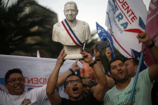Des partisans du candidat à la présidentielle Sebastian Piñera brandissent un buste de Pinochet, à Santiago, le 17 décembre 2017.