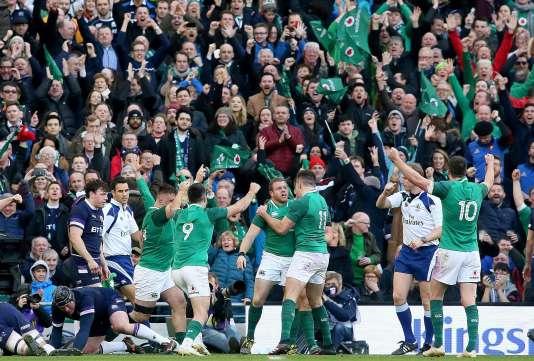 L'IrlandaisSean Cronin fête son essai au milieu de ses coéquipiers, le 10 mars 2018, contre l'Ecosse. / AFP / Paul FAITH