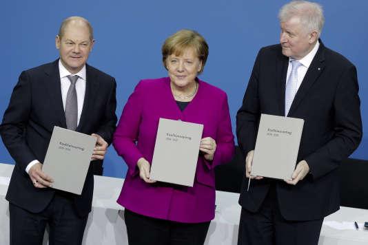 Angela Merkel, entourée à gauche d'Olaf Scholz, vice-chancelier et nouveau ministre des finances, et, à droite, d'Horst Seehofer, le nouveau ministre de l'intérieur, lors de la signature de l'accord de coalition, àBerlin, le 12 mars.