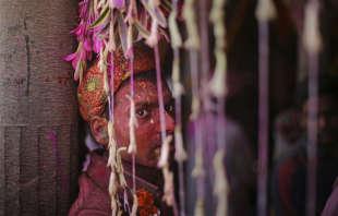 Un adepte se repose à l'écart, au temple Ladali, devant la procession du festival, à Barsana, dans l'Etat de l'Uttar Pradesh (Inde), le 24février.