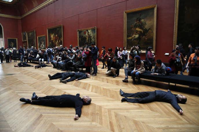 Des militants allongés sur le sol du Louvre pour protester contre Total, l'un de ses mécènes, le 12 mars.