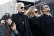 "(FILES) This file photo taken on December 9, 2017 shows Laeticia Hallyday, (3R), wife of late French singer Johnny Hallyday, her children Jade (L) and Joy, son of Johnny Hallyday David Hallyday (R), daughter Laura Smet (4R) standing during the funeral ceremony for Johnny Hallyday at the Eglise de la Madeleine (La Madeleine Church) in Paris. The daughter of French rock legend Johnny Hallyday caused a sensation on February 12, 2018 by challenging his will after he left everything to his fourth wife Laeticia, who was 32 years his junior. Smet said she was ""stupefied and hurt"" after learning that she and her half-brother David -- the singer's only two biological children -- had been left nothing by the ""French Elvis"". Instead, all of Hallyday's wealth and the rights to his catalogue will eventually go to the girls he and Laeticia adopted in Vietnam, Jade and Joy. / AFP / Yoan VALAT"