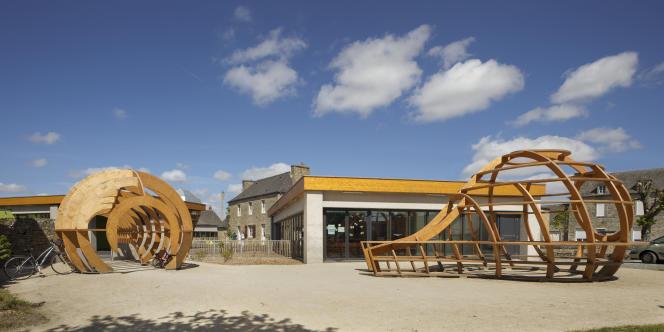 Deux « Extensions de générosité» en bois sculpté, destinées à l'accueil et à la rencontre et, au centre, la salle de partage de l'école Le Blé en herbe,à Trébédan, dans les Côtes-d'Armor (2015).