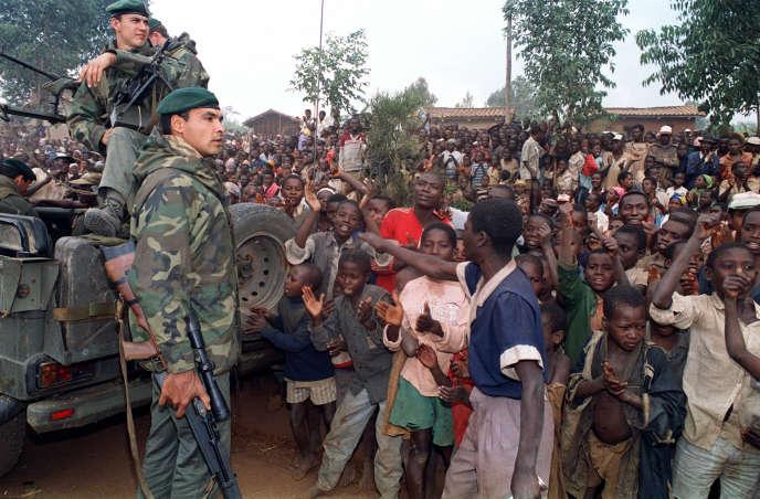 Des réfugiés hutu saluent les officiers de marines français arrivant dans un camp, le3juillet1994.