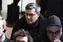 Julien Coupat à son arrivée au palais de justice de Paris, le 13 mars. A droite, le masque est à l'effigie du procureur Olivier Christen qui représente le ministère public pendant le procès et a, dirigé la section antiterroriste du parquet de 2010 à 2014.
