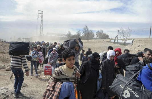 Fuite de civils de la Ghouta orientale, depuis la ville de Hammouriyé, sur une photo datée du 15 mars et publiée par l'agence officielle du régime syrien, SANA.