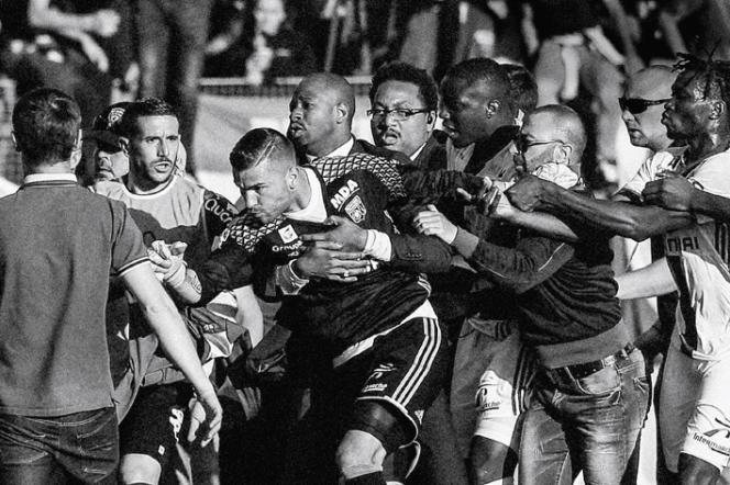 Un agent de la sécurité retientle gardien de but lyonnais Anthony Lopes à la mi-temps, au stade Armand-Cesari, à Bastia, le 16 avril 2017.
