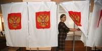 Installation d'isoloirs dans un bureau de vote à Moscou, le 16 mars.