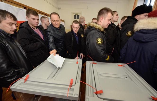 Un électeur dépose son bulletin de vote tandis que d'autres font la queue,à Vladivostok, en Extrême-Orient russe, le 18 mars.