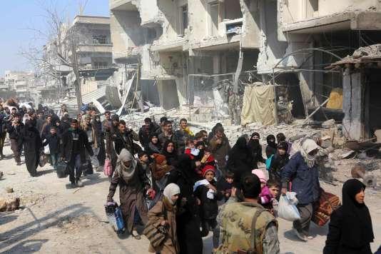 Des civils syriens quittent la ville de Jisrin, dans la Ghouta oreintale, le 17 mars.