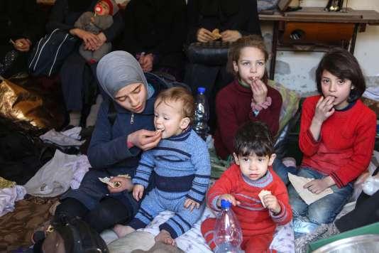 Une jeune femme nourrit des enfants qui s'apprêtent à être évacués de la ville de Jisrin, dans la Ghouta orientale bombardée, le 17 mars.