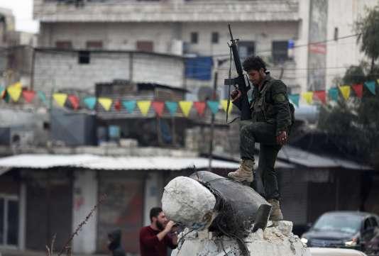 Un rebelle soutenu par la Turquie piétine la statue de Kawa le forgeron, personnage mythique adulé des Kurdes, le 18 mars à Afrin.
