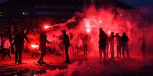 Marseille's supporters burn flares on March 18, 2018, in front of the Velodrome Stadium in Marseille, southeastern France, before the French L1 football match between Marseille (OM) and Lyon (OL). / AFP / ANNE-CHRISTINE POUJOULAT