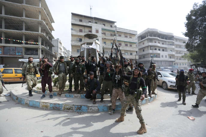 Des supplétifs de l'armée turque célèbrent leur victoire, dans la ville d'Afrin, le 18 mars.