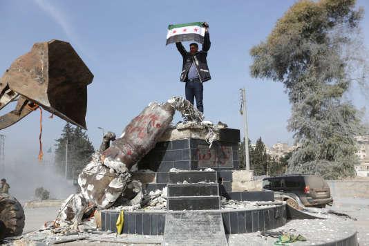 Un combattant de l'Armée syrienne libre brandissant le drapeau de sa faction devant une statue kurde renversée.