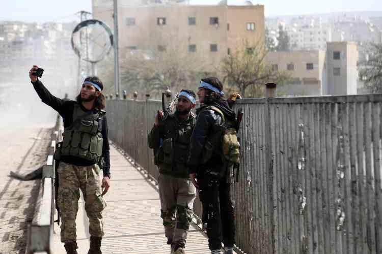 Des rebelles syriens, alliés des forces turques, se prennent en photo dans la ville d'Afrin, le 18 mars.