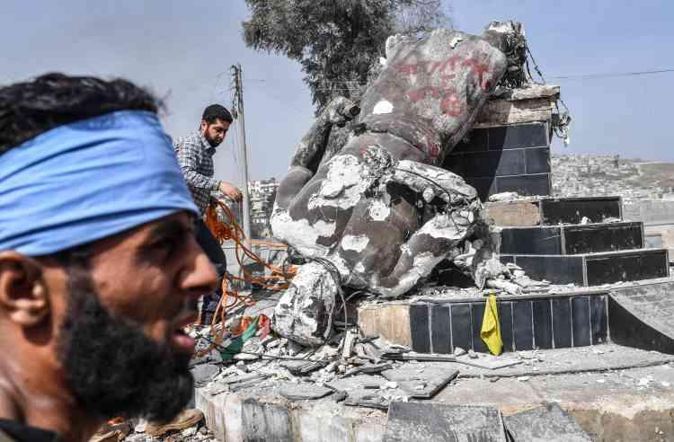 Des rebelles syriens mettent à bas la statue du forgeron Kawa, héros mythologique kurde, qui ornait jusqu'ici un rond-point de la ville.