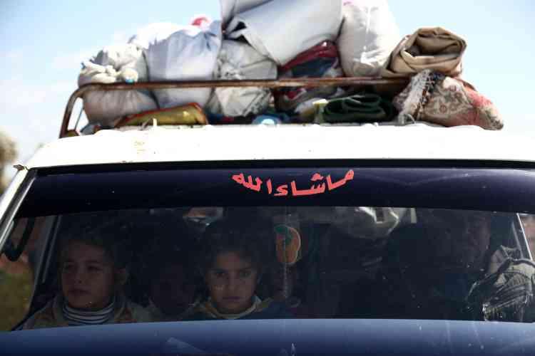 Des Syriens attendent à un check-point dans le village d'Anab, le 17 mars.