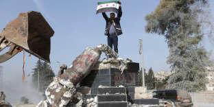Un membre de l'Armée syrienne libre, lors de la reprise d'Afrin par Ankara,devant unestatue kurde détruite, le 18 mars 2018.