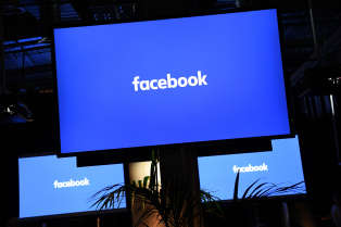 """A Facebook logo is pictured on a screen ahead of a press conference to announce the launch of it's latest product """"Workplace"""", in central London on October 10, 2016. Social network giant Facebook launched new global product Workplace, a platform that it hopes will replace intranet, mailbox and other internal communication tools used by businesses worldwide. It is intended to compete with similar office communication products including Microsoft's Yammer, Salesforce's Chatter and Slack. / AFP PHOTO / Justin TALLIS"""