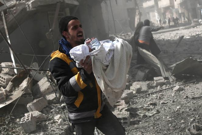 Un Syrien transporte un bébé sauvé des décombres des bâtiments suite aux bombardements dans la ville rebelle de Hamouria, dans la région de la Ghouta orientale, le 19 février 2018.