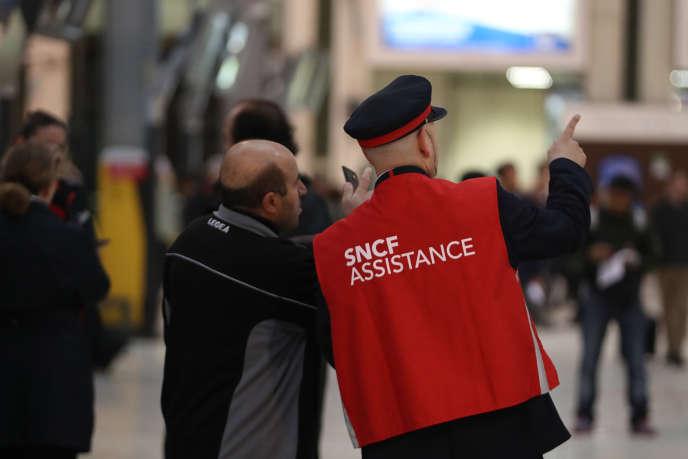Un employé de la SNCF renseigne un voyageur, à la Gare de Lyon à Paris, lors de la grève de juin 2016.