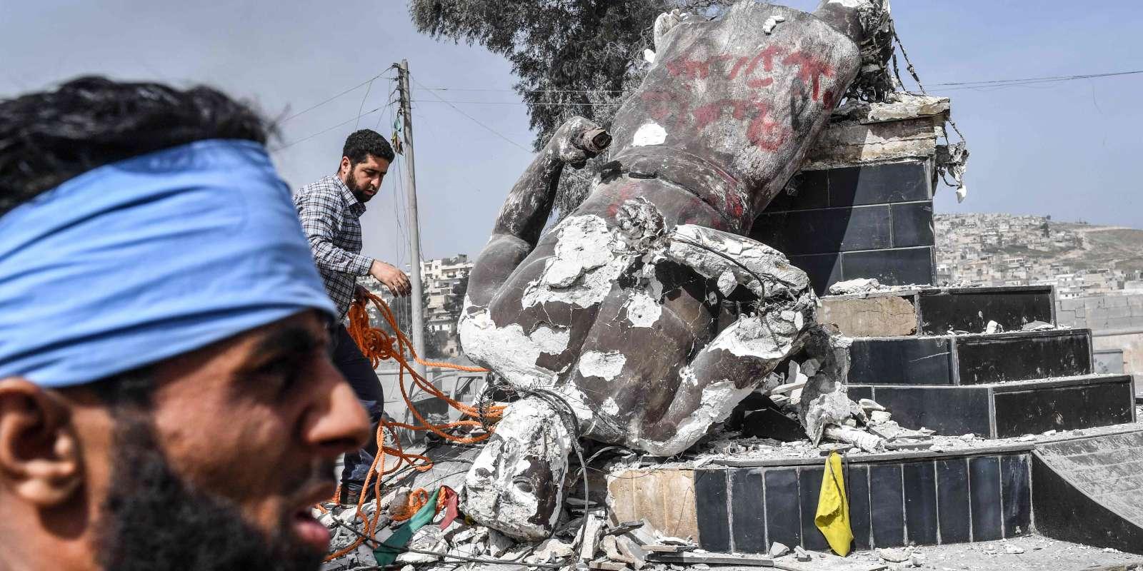 Des rebelles syriens soutenus par la Turquie abattent une statue de Kawa le forgeron, personnage mythique considéré comme un héros par les Kurdes, le 18 mars à Afrin.