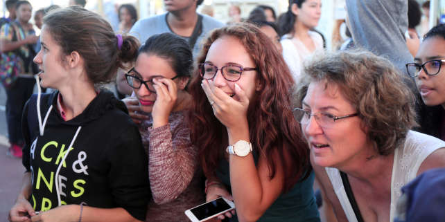 Students react as they check the results of the baccalaureat exam (high school graduation exam) on July 5, 2017 in Saint-Denis, on the French indian ocean island of La Réunion. / AFP PHOTO / Richard BOUHET