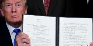 Donald Trump montre le mémorandum surles droits de propriété intellectuelle concernant les produits de haute technologie en provenance de Chine, à la Maison Blanche, à Washington, le 22 mars 2018.