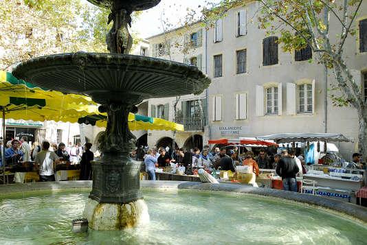 La fontaine de la place aux Herbes, à Uzès, un jour de marché.