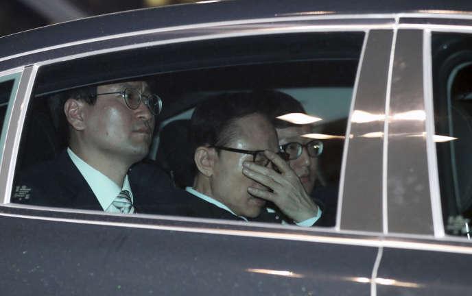 Lee Myung-bak (au centre) lors de son arrestation, à Séoul, le 22 mars 2018.