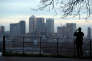 FILE PHOTO: A man takes a photograph of the Canary Wharf financial district from Greenwich Park in London, Britain, January 22, 2017. REUTERS/Hannah McKay/File Photo